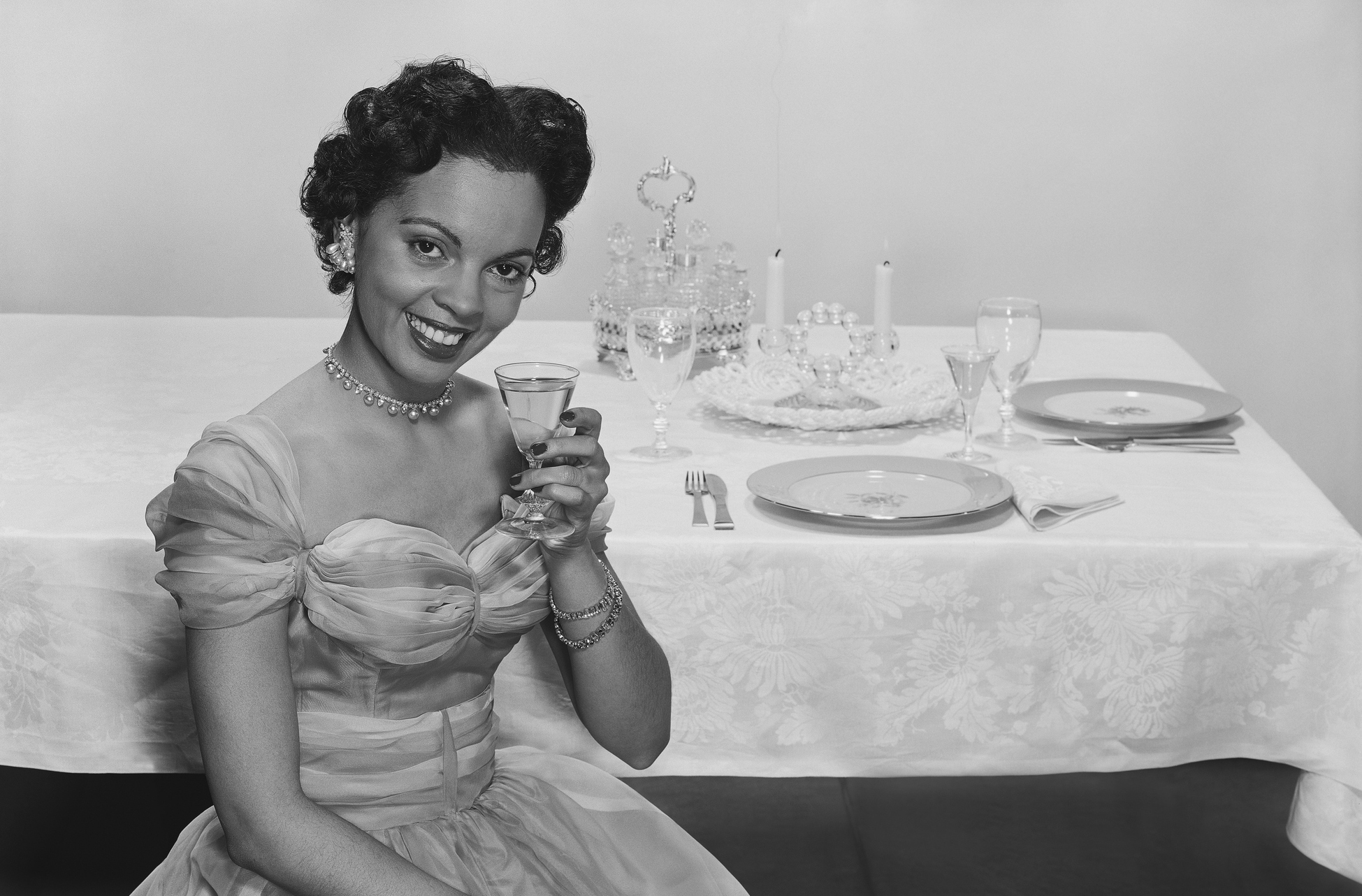 Woman holding glass of drink, smiling, portrait